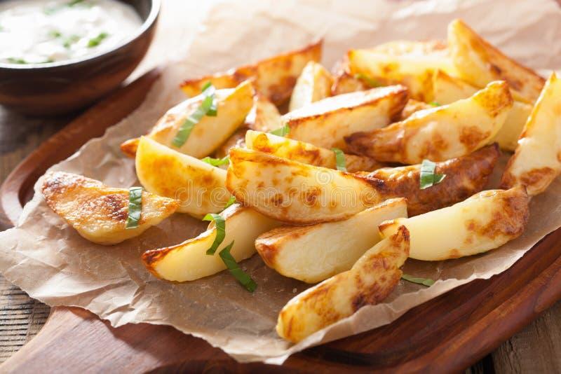 Cuñas cocidas de la patata con la inmersión del yogur fotografía de archivo