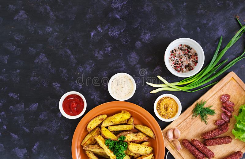 Cuñas cocidas de la patata con las salchichas y las especias Visi?n superior foto de archivo