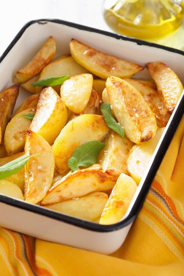Cuñas cocidas de la patata en plato de la hornada del esmalte imagenes de archivo