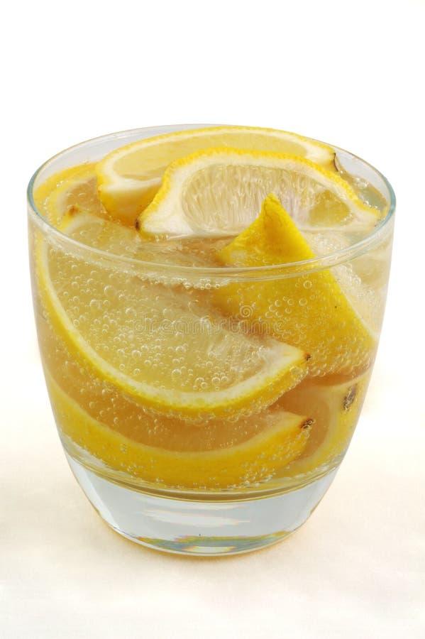 Cuñas de limón en el agua mineral de cristal imagen de archivo