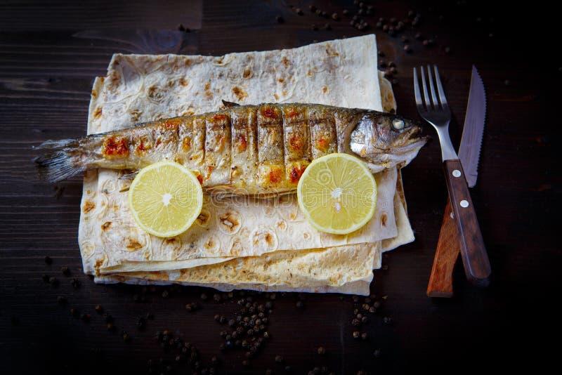 Cuñas fritas de la trucha, del pan Pita y de limón Platos, mariscos o pescados y pita de la parrilla para el menú del restaurante foto de archivo