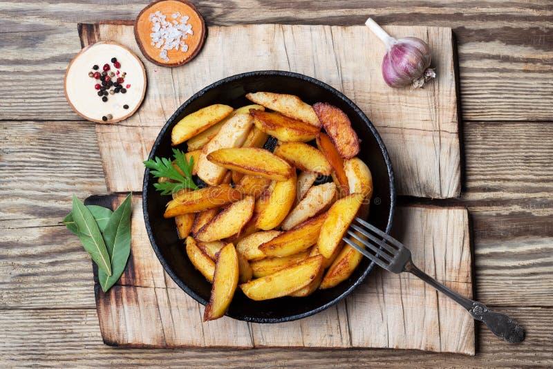 Cuñas fritas de las patatas en una cacerola en la tabla de madera fotos de archivo libres de regalías