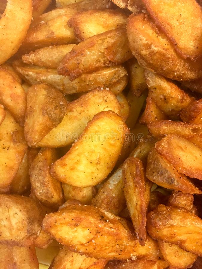 Cuñas fritas de oro curruscantes de la patata foto de archivo