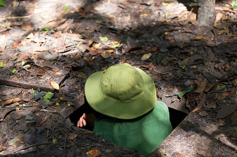 CU CHI, VIETNAM - April 17, 2015: A guide demonstrating how a Vietcong hide into the Tunnel royalty free stock images