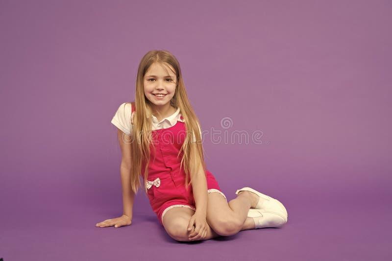 Cu?nteme su historia La cara feliz de la muchacha se sienta en el piso listo escucha fondo de la violeta de la historia Muchacha  fotos de archivo