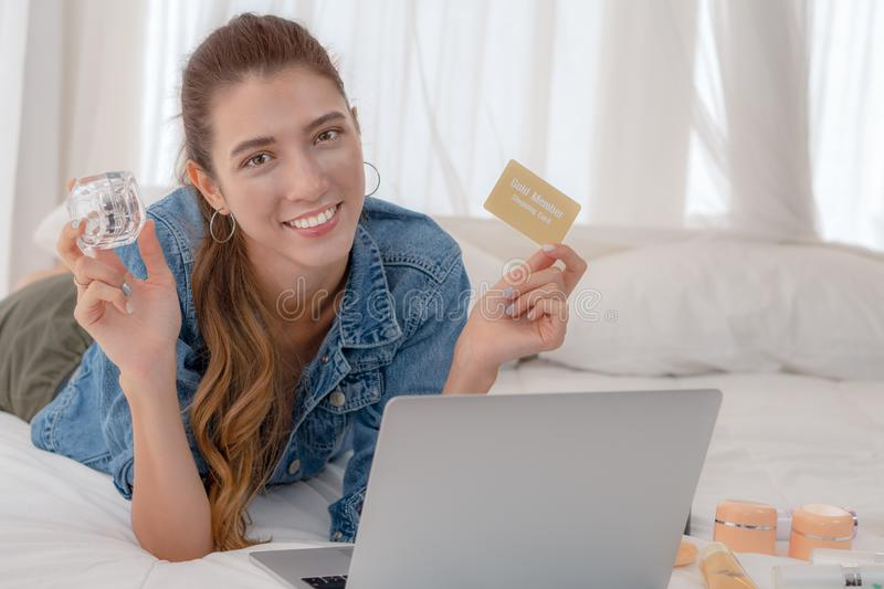 Cuacasian woman laying on bed holding shopping card and a case of cosmetic on hand with laptop computer inconcept of shopping royalty free stock photography
