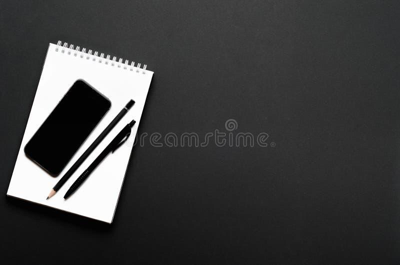 Cuaderno abierto blanco con el l?piz, la pluma y el smartphone negros en fondo negro Escritorio de oficina, efectos de escritorio imágenes de archivo libres de regalías