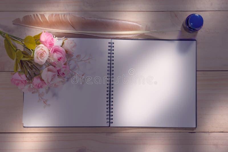 Cuaderno abierto con la pluma de la pluma en la tabla de madera imágenes de archivo libres de regalías