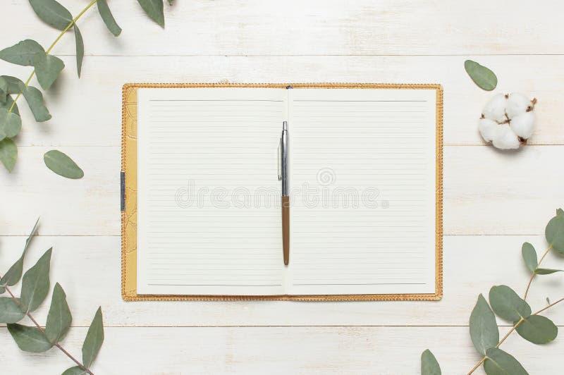 Cuaderno abierto con las páginas en blanco, la pluma, la ramita del eucalipto y las flores del algodón en la endecha plana de mad fotografía de archivo libre de regalías