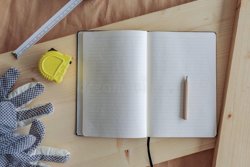 Cuaderno abierto con las páginas en blanco en taller de la carpintería fotos de archivo