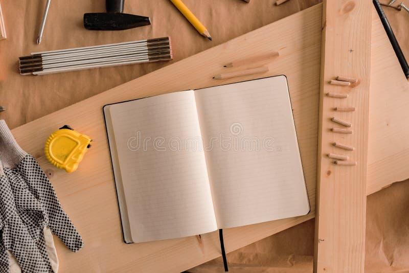 Cuaderno abierto con las páginas en blanco en taller de la carpintería foto de archivo libre de regalías