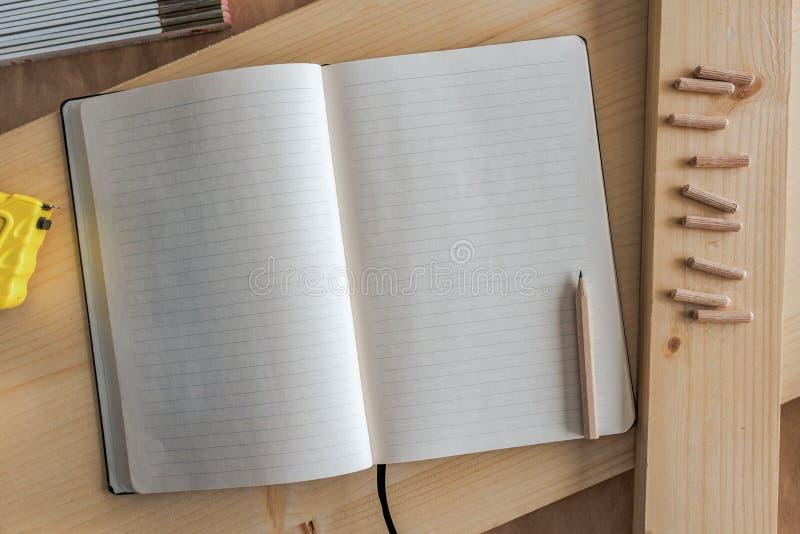 Cuaderno abierto con las páginas en blanco en taller de la carpintería fotos de archivo libres de regalías