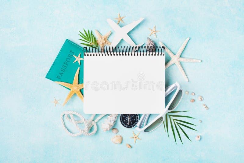 Cuaderno abierto con los accesorios en la opinión de sobremesa en colores pastel azul Fondo de planificaci?n de las vacaciones de imagenes de archivo