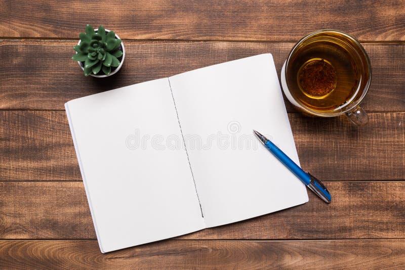 cuaderno abierto de la visión superior con las páginas en blanco al lado de la taza de café en la tabla de madera aliste para aña imagenes de archivo