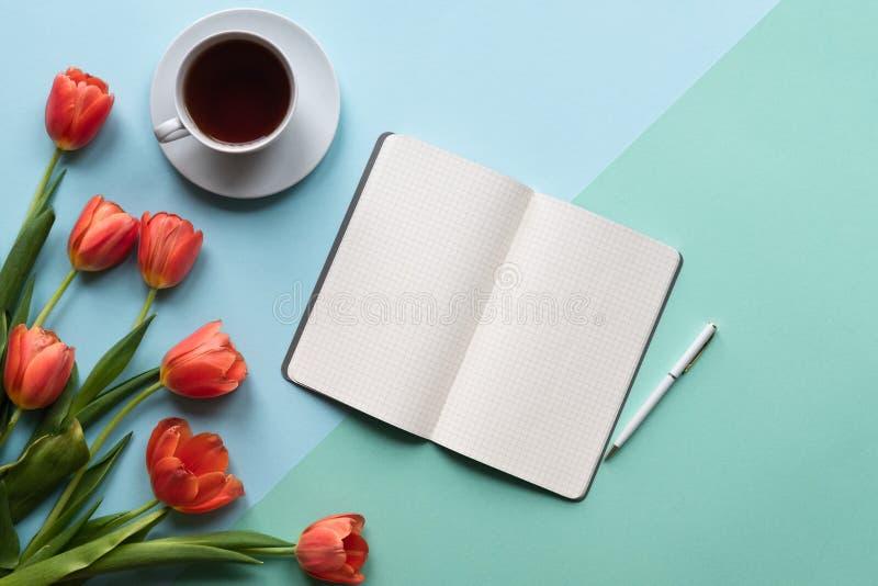 Cuaderno abierto en fondo azul con los tulipanes, la taza de té y el ordenador portátil Copie el espacio fotografía de archivo libre de regalías