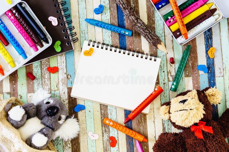 Cuaderno abierto y muñecas lindas de la koala y del mono, creyones del espacio en blanco encendido imagen de archivo libre de regalías