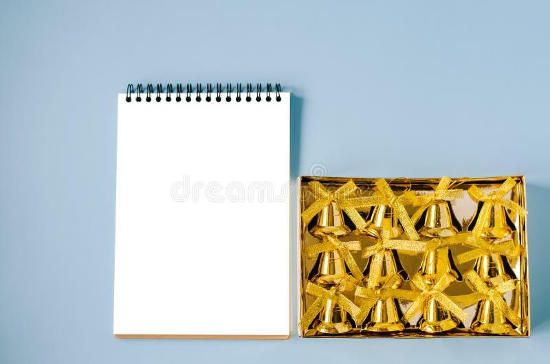 Cuaderno aislado con una caja de campanas de oro fotografía de archivo