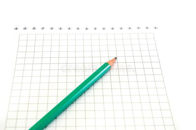 Cuaderno blanco con un lápiz en un fondo blanco fotografía de archivo