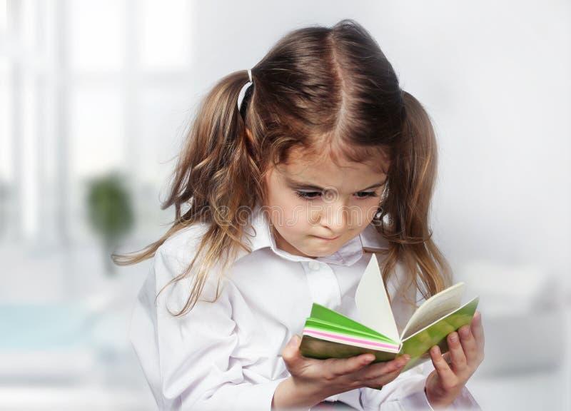 Cuaderno caucásico de la lectura de la muchacha del niño interior imagenes de archivo