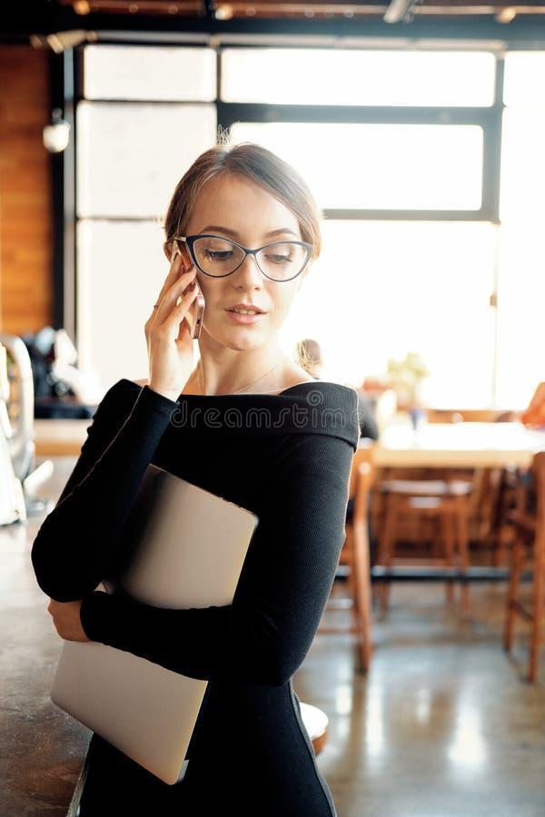 Cuaderno caucásico joven de la tenencia de la empresaria en manos y el hablar en el teléfono en la oficina, encargado serio de la foto de archivo