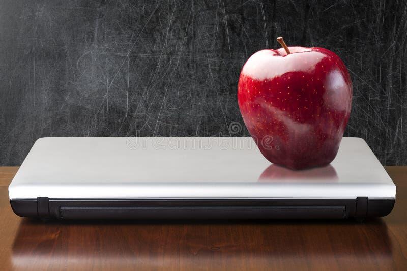 Cuaderno cerrado rojo de Apple de la pizarra vacía fotografía de archivo