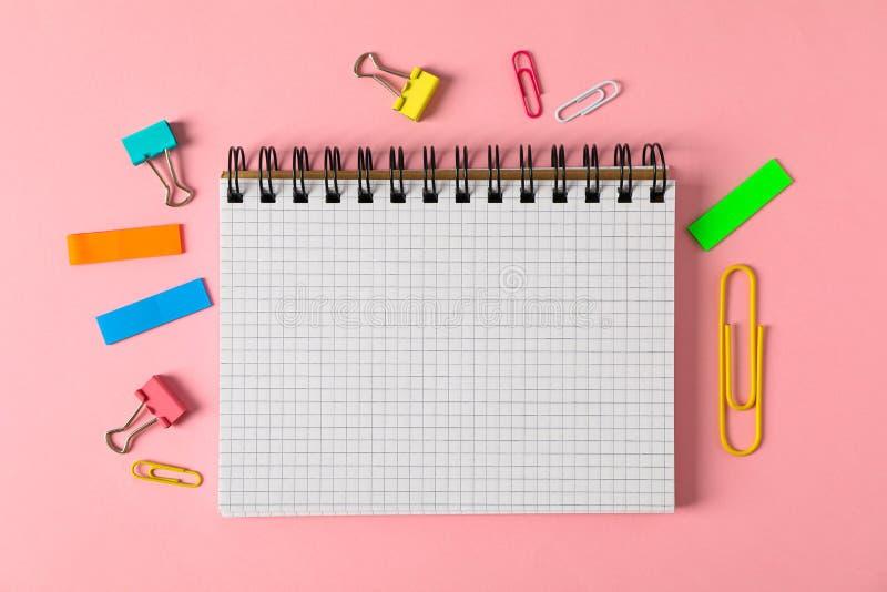 Cuaderno, clips y etiquetas engomadas en fondo del color fotos de archivo