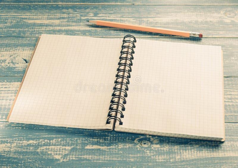 Cuaderno comprobado en la madera fotografía de archivo libre de regalías