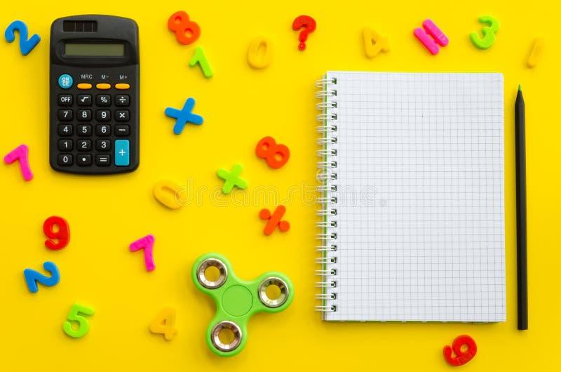 Cuaderno con con el hilandero multicolor de los números, de la calculadora y de la mano fotografía de archivo libre de regalías