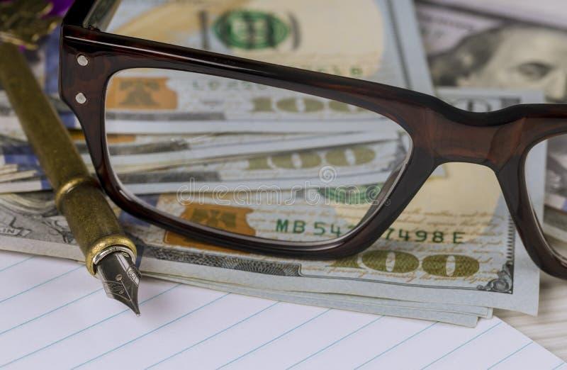 Cuaderno con contabilidad empresarial financiera de los d?lares, de la pluma y de los vidrios imagen de archivo