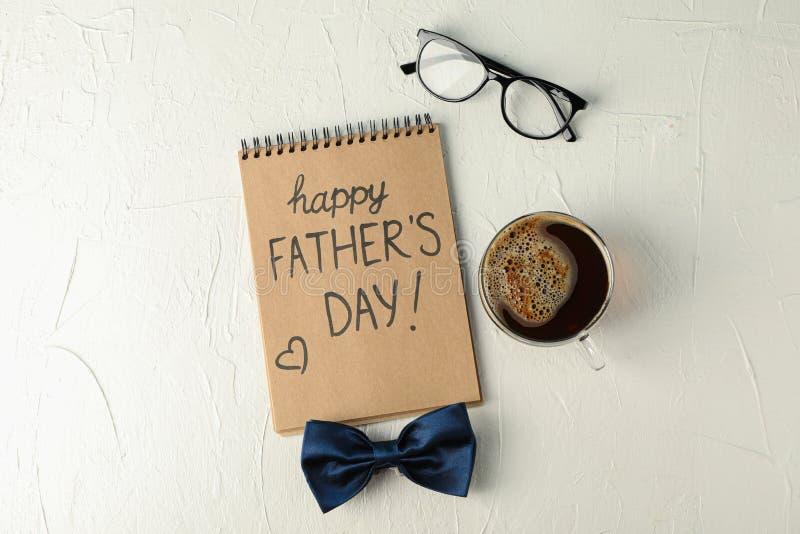 Cuaderno con d?a de padres feliz de la inscripci?n, la corbata de lazo azul, la taza de caf? y los vidrios en el fondo blanco, es foto de archivo libre de regalías