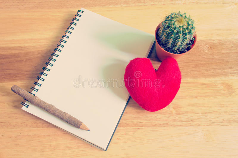 Cuaderno con el corazón y el cactus en fondo de madera foto de archivo libre de regalías