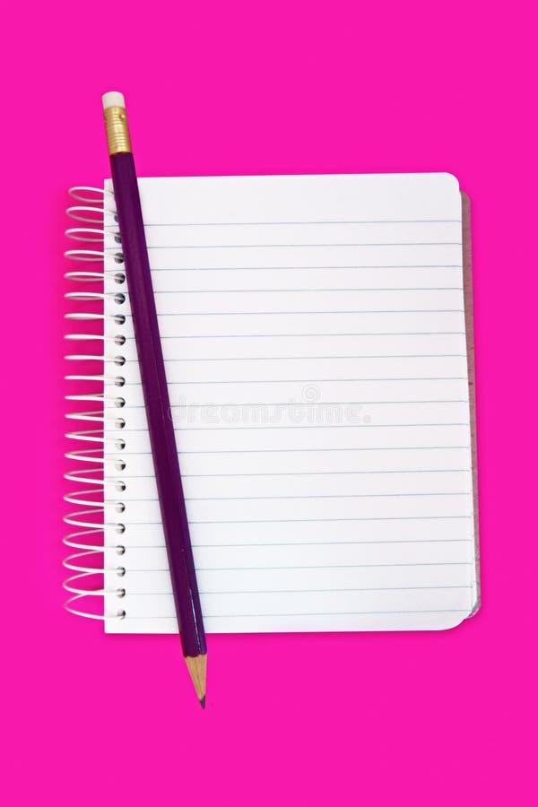 Cuaderno con el lápiz en color de rosa fotografía de archivo