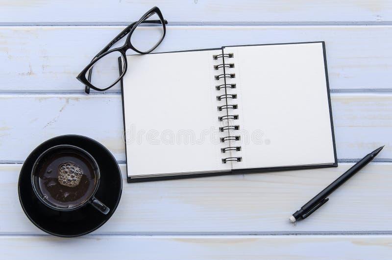 Cuaderno con el lápiz, vidrios y una taza de coffie en un escritorio de madera imagen de archivo