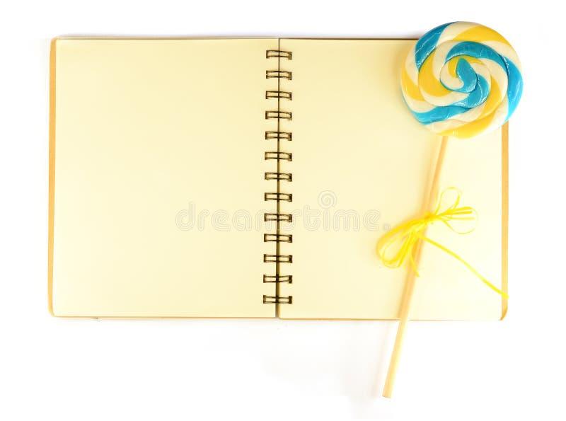 Cuaderno con el papel y el lollypop alineados pálidos imagen de archivo