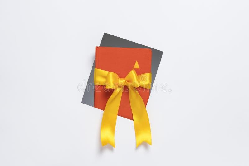 Cuaderno con la cinta del regalo que sale del marco en el fondo blanco fotos de archivo libres de regalías