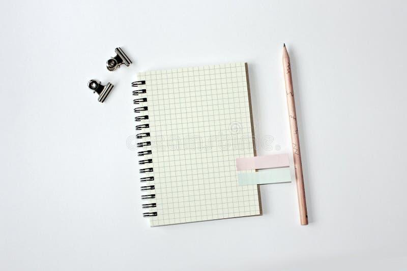 Cuaderno con la línea, el lápiz pegajoso del papel, madera y el clip de papel del metal imagenes de archivo