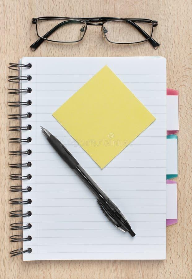 Cuaderno con la nota pegajosa en blanco sobre una oficina o un escritorio casero, con el espacio de la copia imagen de archivo libre de regalías