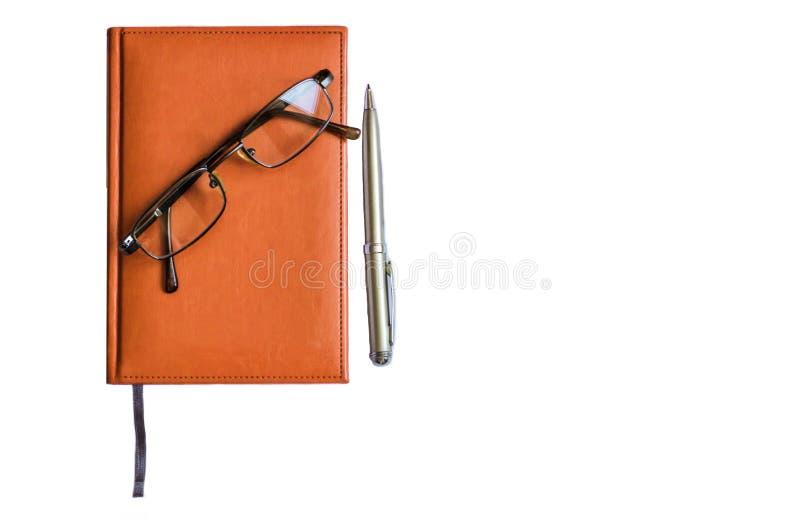 Cuaderno con la pluma que miente encendido foto de archivo