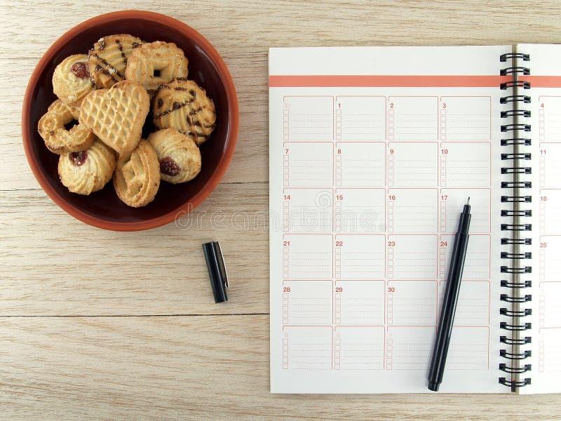 Cuaderno con la pluma y la pila negras de galletas de la galleta en placa marrón de la cerámica en piso de madera de la tabla fotos de archivo libres de regalías