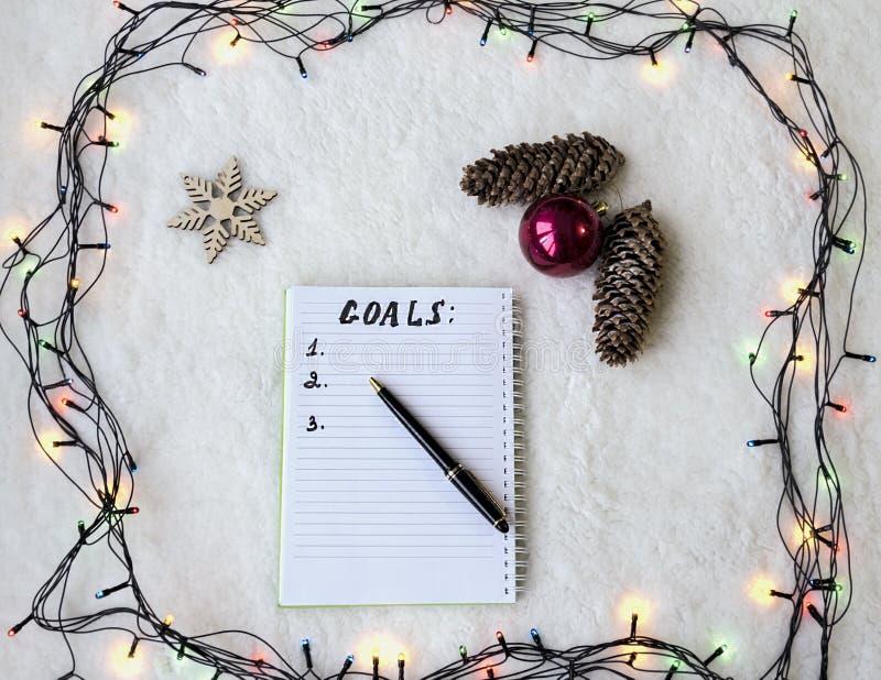 Cuaderno con la pluma y teléfono en el fondo de la guirnalda de la Navidad imágenes de archivo libres de regalías
