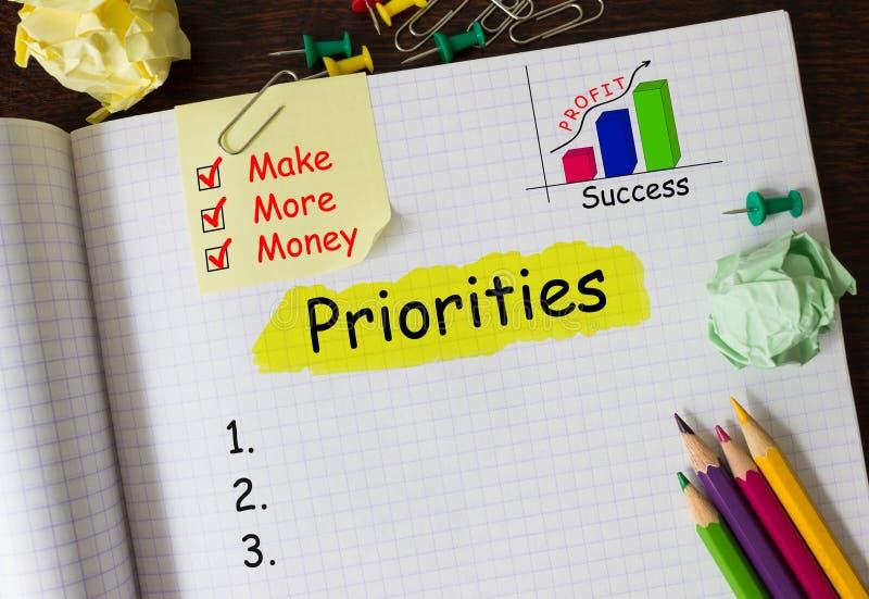 Cuaderno con las herramientas y las notas sobre prioridades imagenes de archivo