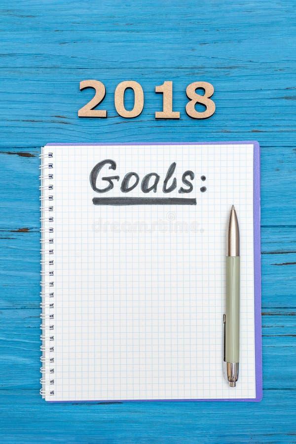 Cuaderno con las metas de los Años Nuevos para 2018 con una pluma y los números 2018 en una tabla de madera azul imagenes de archivo