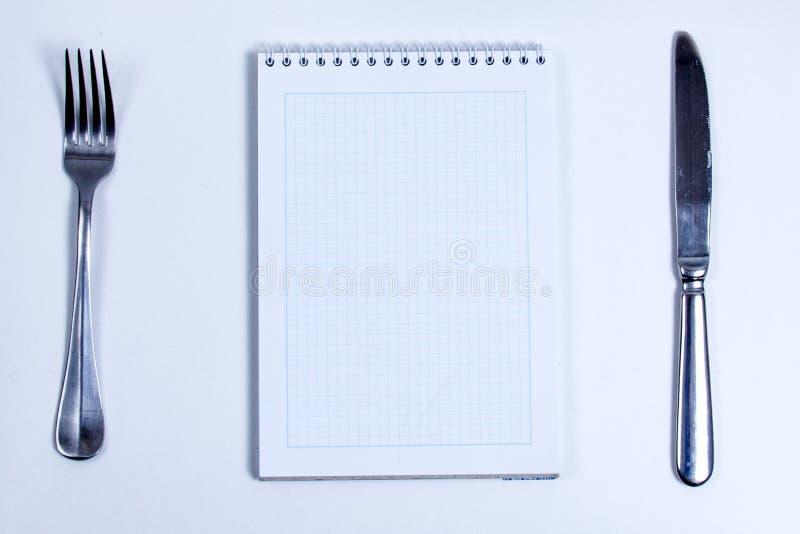 Cuaderno con los cubiertos de plata Cuaderno en blanco alineado con espiral y cubiertos de la plata, bifurcación y cuchillo fotografía de archivo