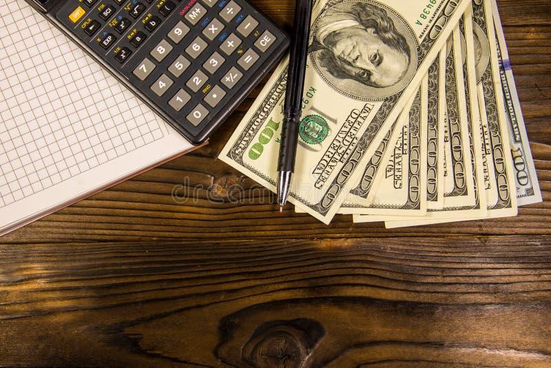 Cuaderno con los dólares, la pluma y la calculadora en el escritorio de madera foto de archivo
