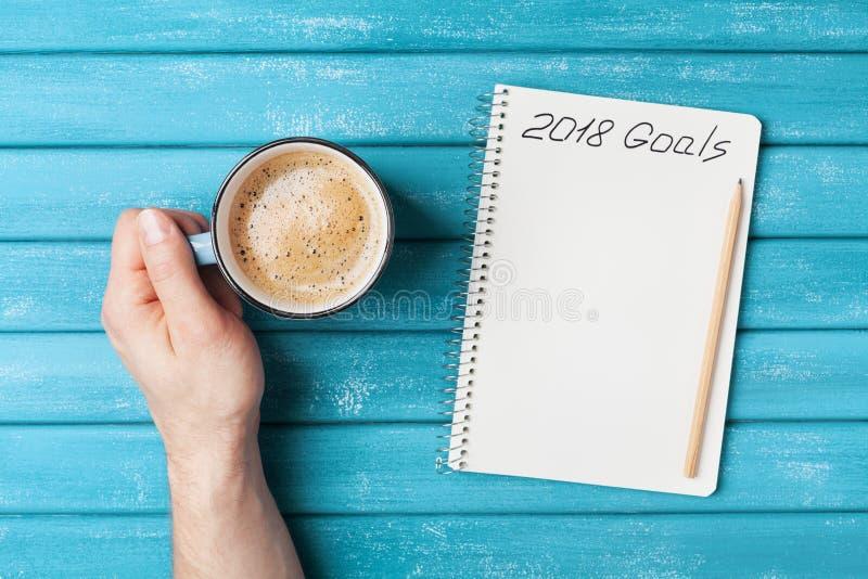 Cuaderno con metas del texto 2018 y taza de café en la visión de escritorio de madera Planeamiento y concepto del negocio Resoluc imagenes de archivo