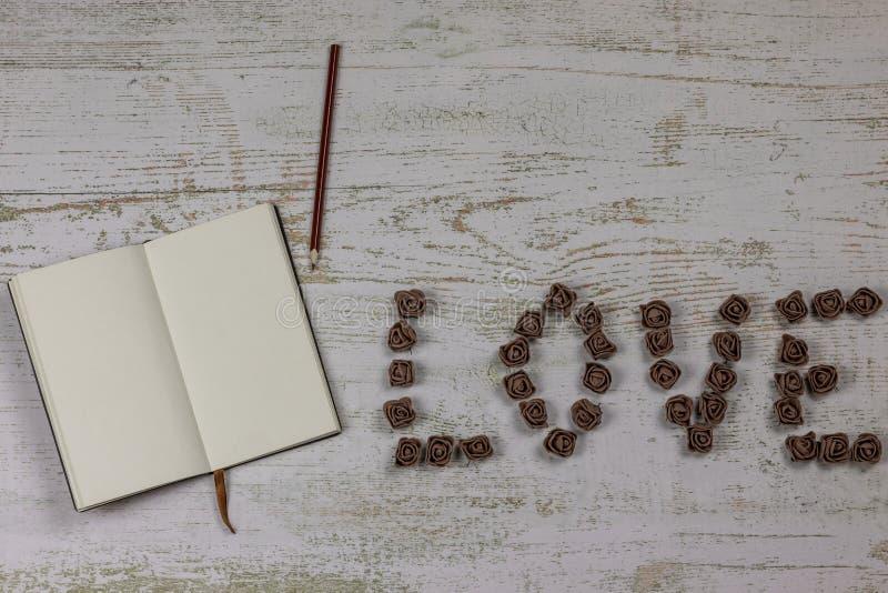 Cuaderno con un lápiz al lado de la inscripción te amo, las letras de rosas oscuras En fondo de madera, foto arriba fotografía de archivo libre de regalías