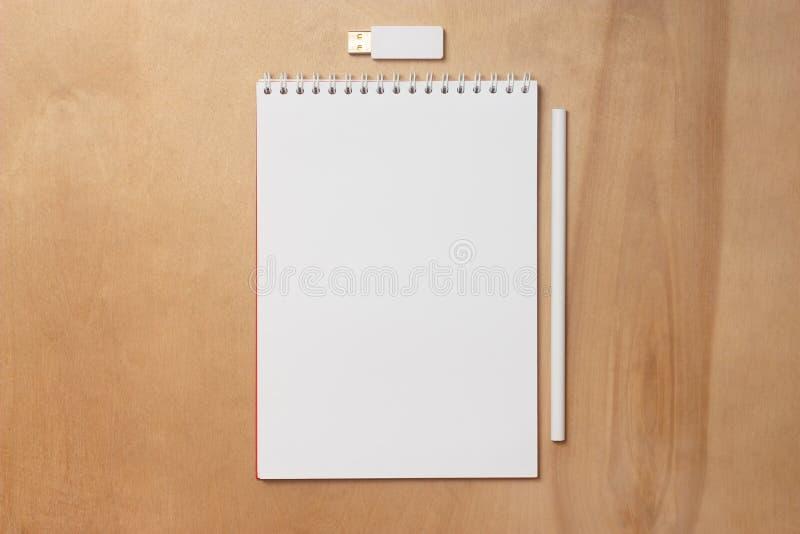 Cuaderno con un lápiz y un palillo de memoria USB Libreta con las hojas blancas en blanco fotografía de archivo libre de regalías