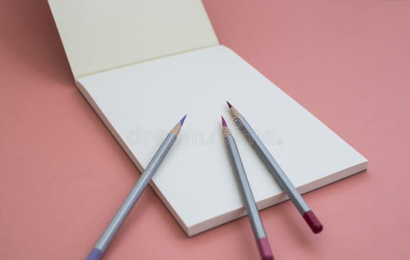 Cuaderno con un l?piz en un fondo rosado imágenes de archivo libres de regalías