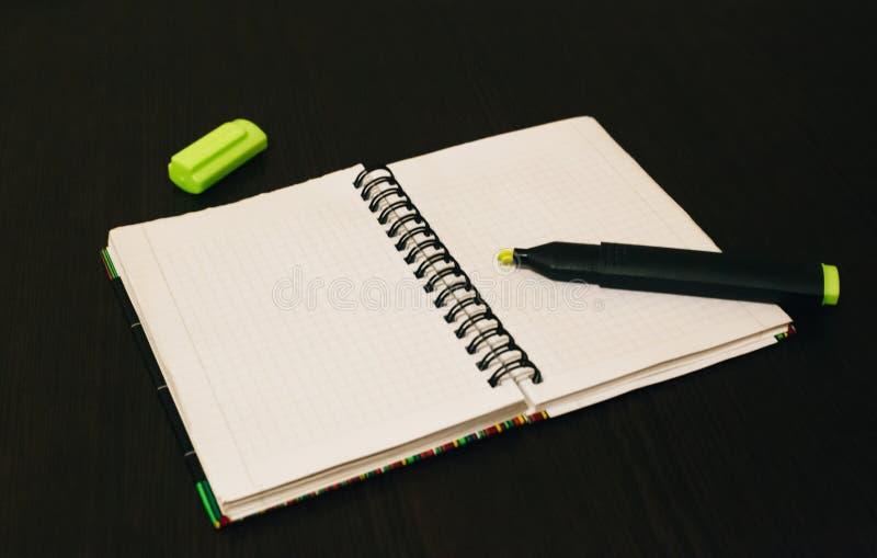 Cuaderno con un marcador en la tabla, abierta en una hoja en blanco fotografía de archivo libre de regalías