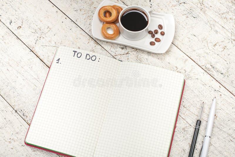Cuaderno con una inscripción, café con los panecillos, las plumas y penci foto de archivo